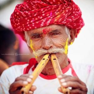 Индус в красной чалме играет на флейте во время Холи. Фото Люся Маратканова.