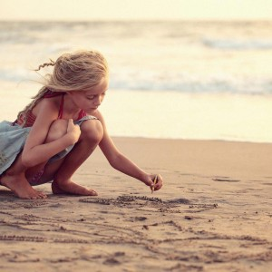 девочка рисует на песке