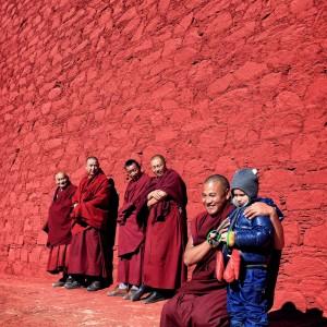Девочка с тибетскими монахами в Тибете у красной стены монастыря Ганден. Фото Люся Маратканова.