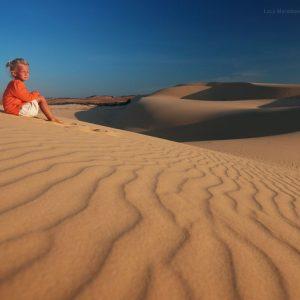 девочка сидит на песчаных дюнах около Муйне во Вьетнаме. Фото Люся Маратканова.