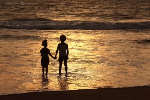Мальчик и девочка у моря держатся за руки на закате. Фото Люся Маратканова.
