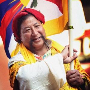 Нарядный тибетец несет флаг Тибета. Фото Люся Маратканова