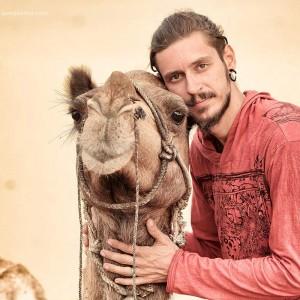 мужчина обнимает верблюда в пустыне Тар