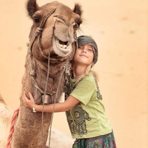 девочка обнимает верблюда в пустыне Тар