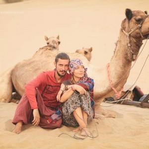 двое на фоне верблюда в пустыне Тар