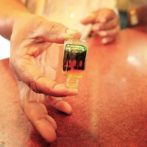 парфюмер на рынке Мапусы (Мапса) смешивает масло
