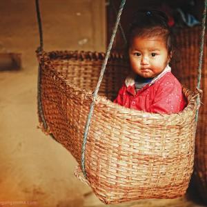 kid in straw cradle in nepal