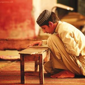 boy is reading koran madrasah school in pakistan