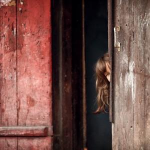 girl is hiding behind the door in russian village