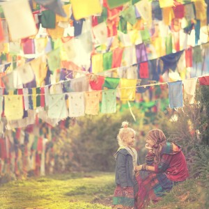 mother and daughter under prayer flags in dharamsala in india