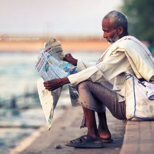 old man is reading a newspaper on the coast in harodvar in india