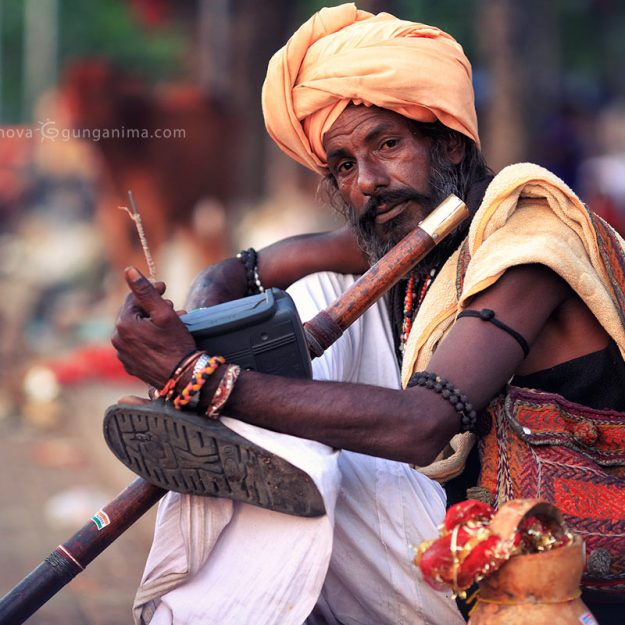 hindu man with flute in turban in haridvar in india