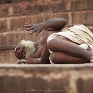 man is lying on the stair in varanasi in india