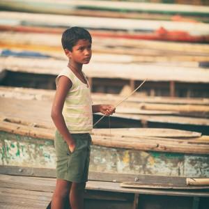 indian boy in boat in varanasi in india