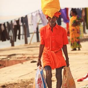 man is taking big bag on head in varanasi in india