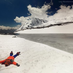 girl is laying in snow in nepali mountains