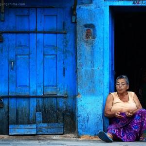женщина на фоне синего дома в катманду в непале