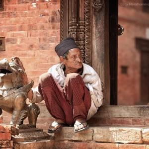 непальский старик рядом со статуей льва в бактапуре