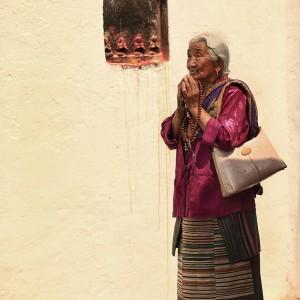 old tibetan woman is praying at the bodnath stupa in nepal