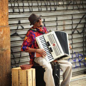 Уличный старый музыкант играет на аккордеоне в бразилии