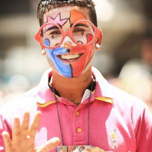Радостный демонстрант с раскрашенным лицом на демонстрации в бразилии