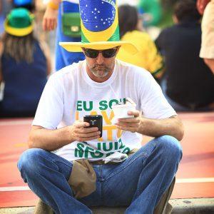 Бразилец в цилиндре смотрит в телефон
