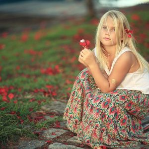 девочка сидит с цветком в руке в парати в бразилии