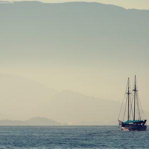 одинокий корабль в море на фоне гор в парати в бразилии