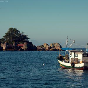 кораблик и маленький каменный остров в море в парати в бразилии