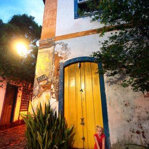 девочка сидит у дверей дома в историческом центре в парати в бразилии