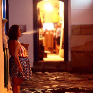 женщина курит на улице вечером в историческом центре парати в бразилии