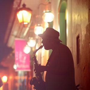 уличный музыкант играет на саксофоне в историческом центре парати в бразилии вечером